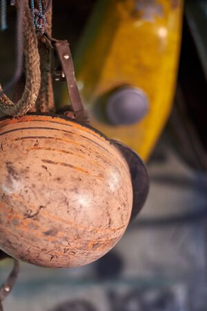 An old vintage scratched motorcycle helmet hangs in a garage. Stockfoto