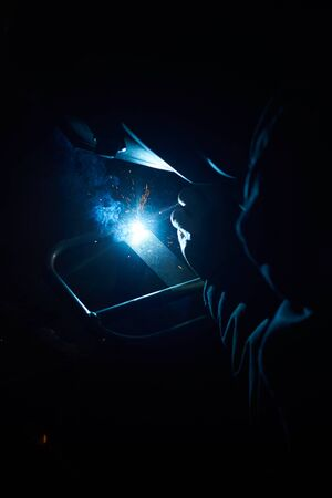 A man in a protective mask carries out welding work in the garage.