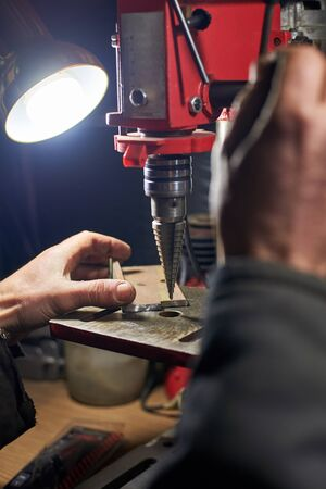 Hands of a man who drills a metal part on a machine tool in a home workshop.