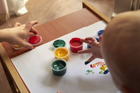 A small boy draws with bright colors with his fingers, the early development of the child.