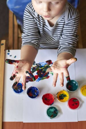 The boy shows dirty hands after drawing with finger paints, the early development of the child.