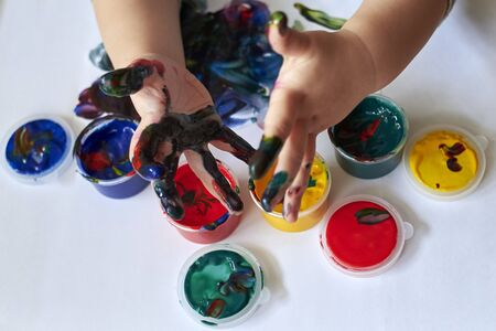 The child shows dirty hands after drawing with finger paints, the early development of the child.
