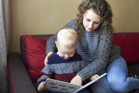 Mom with her little son is reading a book on the sofa at home.