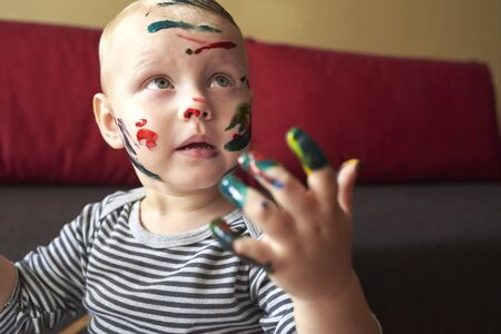 Portrait of nice smeared little boy draws with finger paints, the early development of the child. Stock fotó