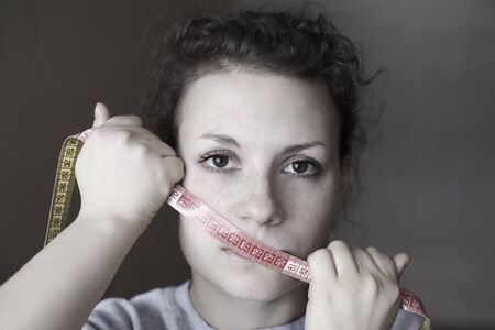 Sad woman with meter on the mouth, topic of losing excess weight, diet and stress. Фото со стока