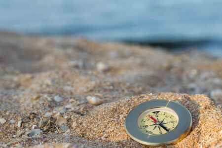 A compass showing the direction lies on sand with seashells