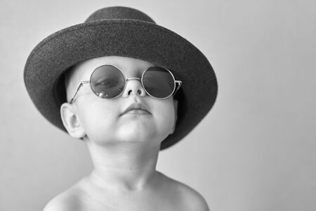 Portrait of a little cute funny boy in a retro hat and round glasses, black and white photo.