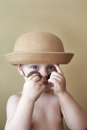 Portrait of a little cute funny boy in a retro hat and round glasses. 免版税图像