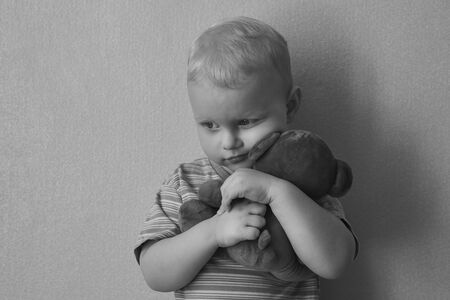 Little lonely boy hugs his teddy bear strongly, the theme of child abuse, black and white photo.