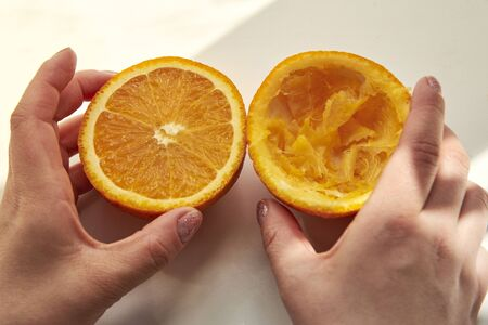 Half a whole and half squeezed orange in a woman's hands after making juice using a manual juicer on a white background.