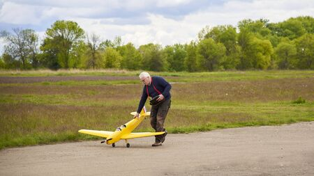 An elderly man launches a radio-controlled aircraft on the runway in the spring.