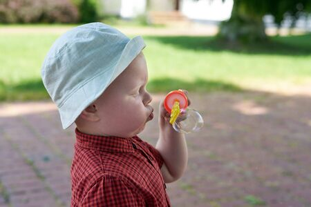 A little boy diligently blows soap bubbles, the theme of summer fun.