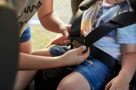 Mom fixes seat belts in a car seat for her baby. Child safety in the car.