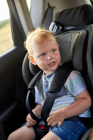 Happy little boy sits in a car seat. Child safety in the car.