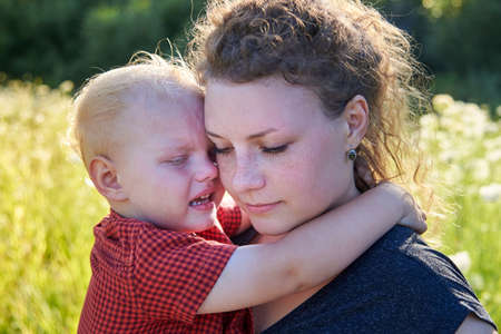 Young mom hugs her crying two years old son. Stockfoto