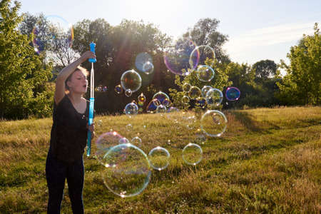 Woman blowing soap bubbles on the meadow in summer, summer fun, summer time.