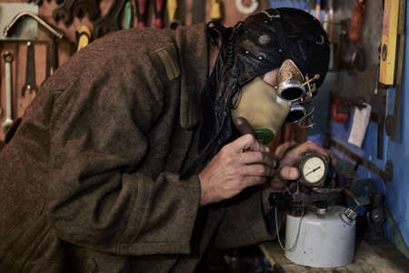 A man in a respirator and glasses in the style of steampunk works with a pressure gauge and a cylinder, postapokalipsis concept.