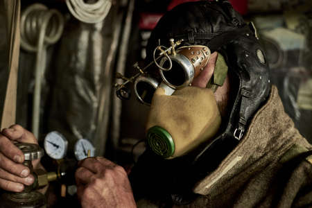 A man in a respirator and glasses in the style of steampunk works with a pressure gauge and a cylinder, postapokalipsis concept. Banque d'images
