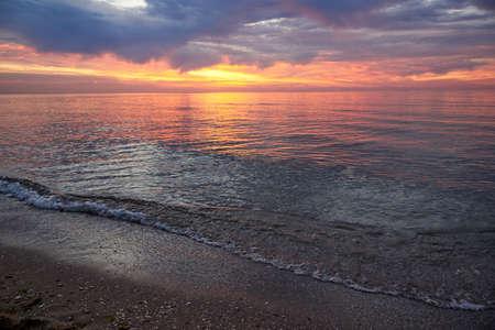 Beautiful cloudy sky at dawn, calm sea water, sand beach landscape. Stock fotó
