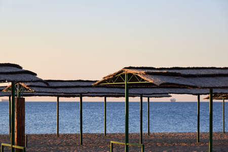 Sea beach at sunrise, nobody, thatched canopies for shelter from the sun.