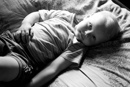 A little boy lies at home on the couch, smiles and looks at the camera, black and white photo. Stock Photo
