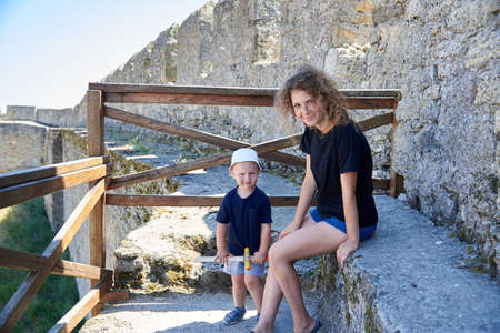 Mom and her little son on the wall of the fortress, summer family trip.