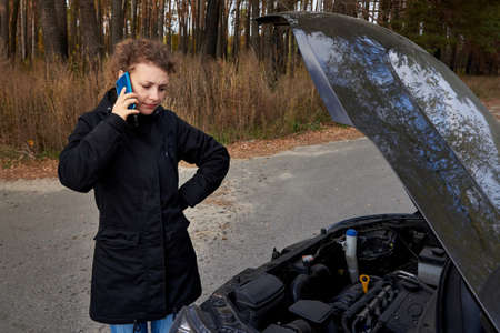 An upset woman stands near her broken car and talking on a cell phone on the road in autumn.