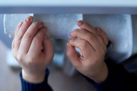 Female hands lie on the radiator, the concept of the heating season.