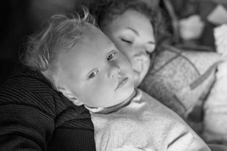 Mom with her little son have a good time at home, moment of tenderness, black and white photo.