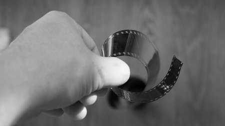 A man holds a negative from an old film camera, close-up.