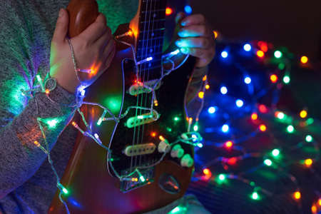 Electric guitar in the hands of a woman against the background of multi-colored garlands.