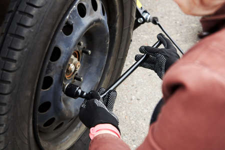 A woman removes the wheel with a key, close-up, trouble on the road.