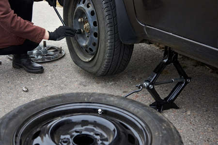 A young woman removes the wheel with a key near her car with a flat tire, trouble on the road.