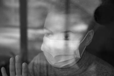 A woman in a medical mask looks out the window, self-isolation during the coronavirus, home quarantine.