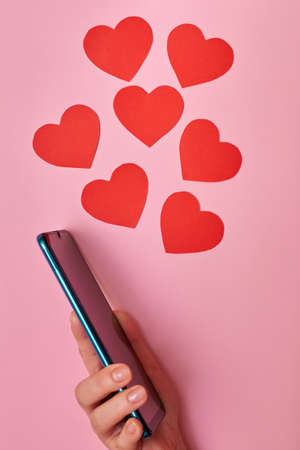 Paper hearts flying out of a smartphone, top view, Valentine's day in the hands of a woman, love and technology concept.