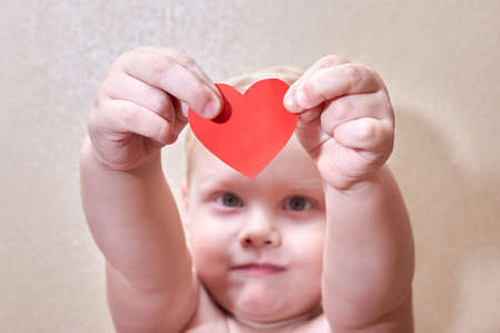 Little smiling boy holding a paper red heart, selective focus, the theme of love and hope.