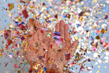 Woman tossing sparkles of confetti from her palms on a blue background, selective focus, the theme of a holiday and a birthday.