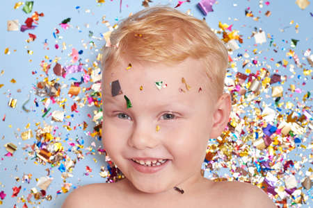 A three-year-old blond smiling boy on a blue background in glitter confetti, a celebration and birthday theme. Banco de Imagens - 162317173