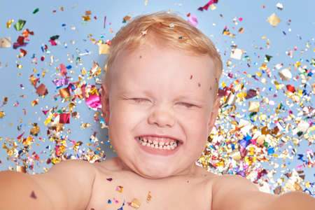 A three-year-old blond smiling boy on a blue background in glitter confetti, a celebration and birthday theme. Banco de Imagens - 162317174