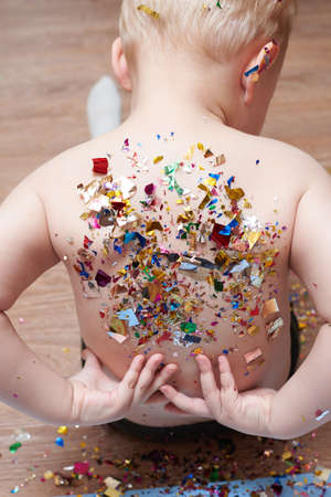 A little boy removes sequins of confetti from his back, a celebration and birthday theme.