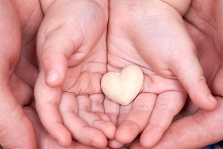 Dad and son hands hold a small plaster heart, family relationship concept.