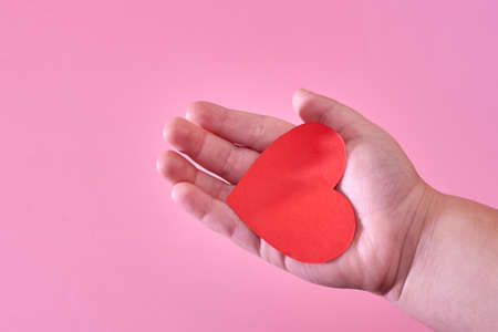 A little boy's hand holds a red paper heart on a pink background, the theme of love and hope.