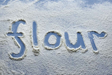 The word flour is written on scattered flour on a blue background, the theme of cooking.