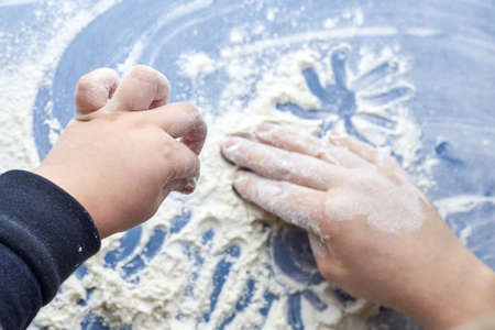 Mom and baby hands paint on flour, home fun.