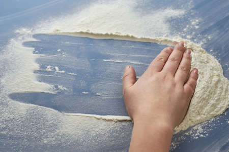 Woman's hand removes flour on blue background, the theme of cooking. 免版税图像