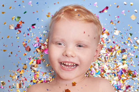 A three-year-old blond smiling boy on a blue background in glitter confetti, a celebration and birthday theme.
