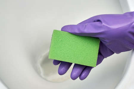 Woman's hand in a glove washes the toilet bowl with a sponge, sanitizing and cleaning the toilet room.