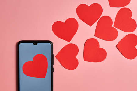 Paper hearts flying out of a smartphone, top view, Valentine's day, love and technology concept.