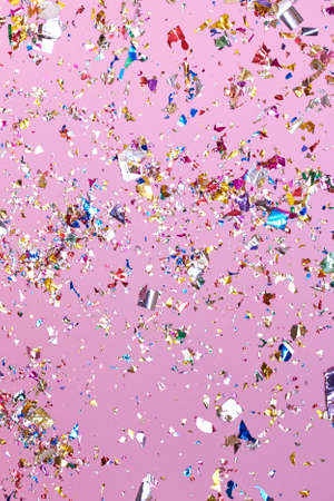 Bright colorful confetti sparkles on a pink background, the theme of a holiday and a birthday.