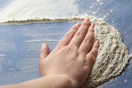 Woman's hand removes flour on blue background, the theme of cooking. Banco de Imagens